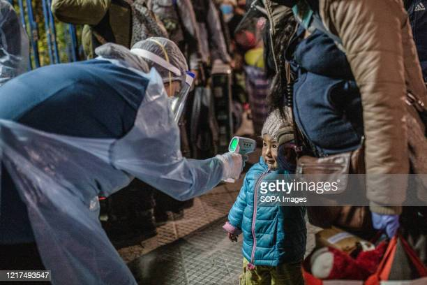 Health personnel measures the body temperature of a kid as a preventive measure during the Coronavirus crisis. Bolivian migrants have been gathering...