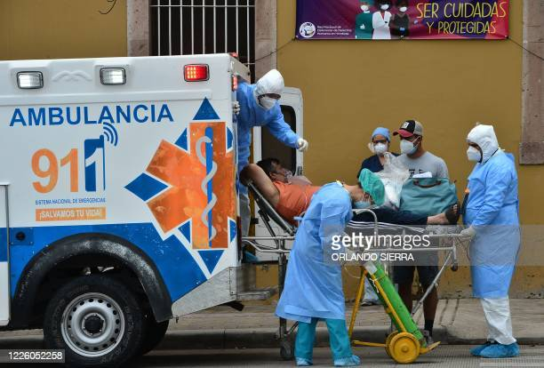 Health personnel of the Permanent Contingency Commission of Honduras assist a man showing symptoms of the novel coronavirus COVID19 in Tegucigalpa on...