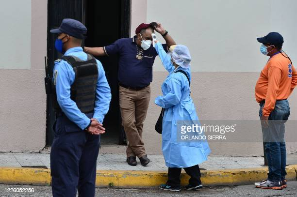 Health personnel take the temperature of a man as they look for suspicious cases of the novel coronavirus COVID19 in Tegucigalpa on July 10 2020 The...