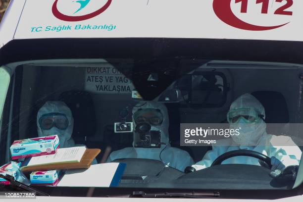 Health personnel wearing protective gear ride in an ambulance carrying passengers and crew of a Turkish Airlines plane from Tehran as they are taken...