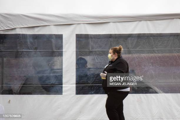 A health professional is seen handling coronavirus tests after swabbing the car behind her at a drive through testing site at the University of...