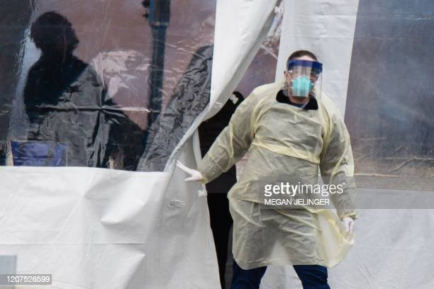 A health professional walks out of a drive through coronavirus testing site at the University of Dayton in Dayton Ohio on March 17 2020 The...