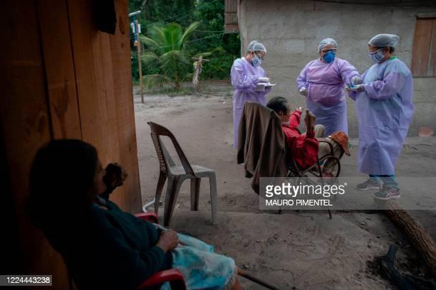 Health professionals administer COVID-19 tests to an elderly indigenous Guarani couple at the Sao Mata Verde Bonita tribe camp, in Guarani indigenous...