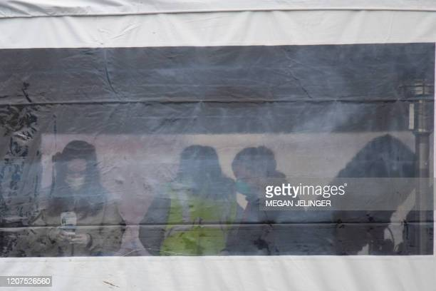 Health professionals are seen handling coronavirus tests at a drive through testing site at the University of Dayton in Dayton Ohio on March 17 2020...
