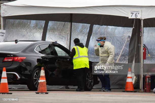 Health professionals conduct coronavirus tests at a drive through testing site at the University of Dayton in Dayton Ohio on March 17 2020 The...