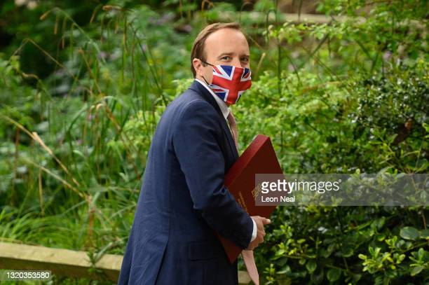 Health Secretary Matt Hancock wearing a Union Jack face mask walks towards the media briefing room in Downing Street on May 27, 2021 in London,...