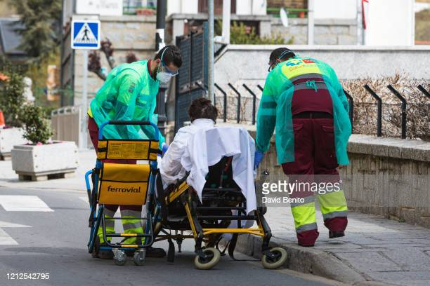 Health staff are seen removing a coronavirus patient from her home and placing her in an ambulance in Cercedilla in the Community of Madrid on March...