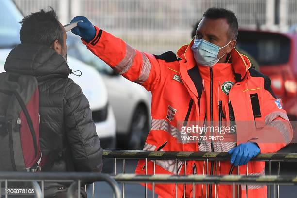 A health staff checks the body temperature of a man arriving at the Juventus stadium before the Italian Serie A football match Juventus vs Inter...