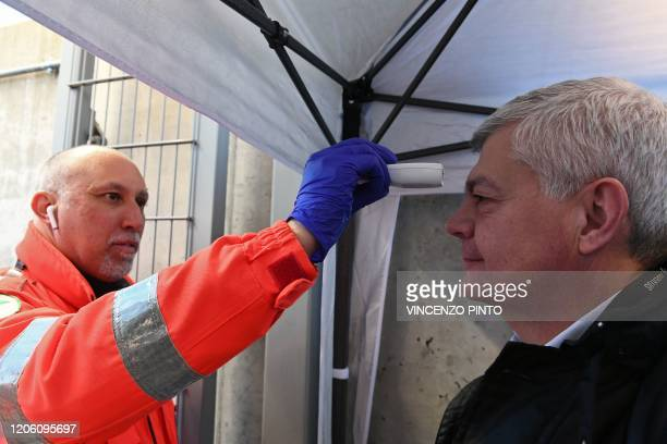 Health staff checks the body temperature of a man arriving at the Juventus stadium before the Italian Serie A football match Juventus vs Inter Milan...