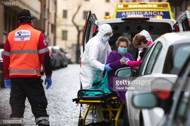 Health staff take a coronavirus patient from her home into an ambulance on April 01, 2020 in Segovia, Spain. Spain ordered all non-essential workers...