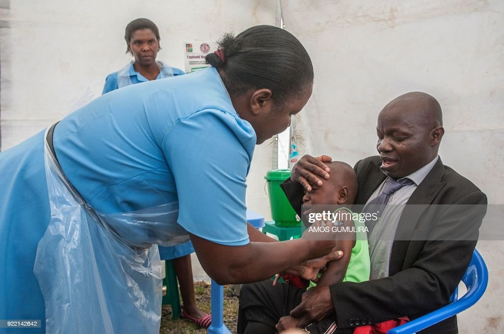Health Surveillance Assistant Mary Memory Chirwa administers the typhoid vaccine to Golden Kondowe, as his father Christopher Kondowe holds him, during the launch of a typhoid vaccination campaign at Ndirande Health Centre in Blantyre, by the Malawi Liverpool Welcome Trust, on February 21, 2018. At least 23,000 children are targeted for vaccination during the campaign period. /