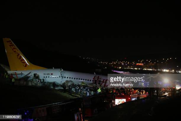 Health teams and fire brigade crews conduct operation at debris of a passenger plane after it skidded off the runway in Istanbul Sabiha Gokcen...