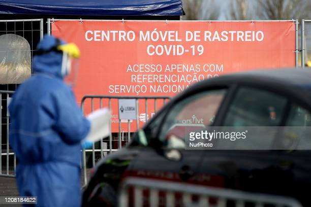 A health technician wearing protective gear interviews people at a COVID19 Coronavirus drivethrough screening center in Lisbon Portugal on March 24...
