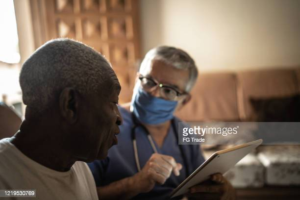 health visitor and a senior man during home visit - using digital tablet - nurse with mask stock pictures, royalty-free photos & images