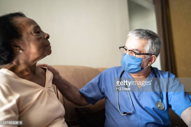 health visitor and a senior woman during home visit - nurse with mask stock pictures, royalty-free photos & images