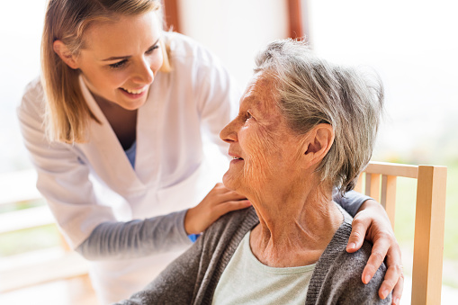 Health visitor and a senior woman during home visit. 870060028