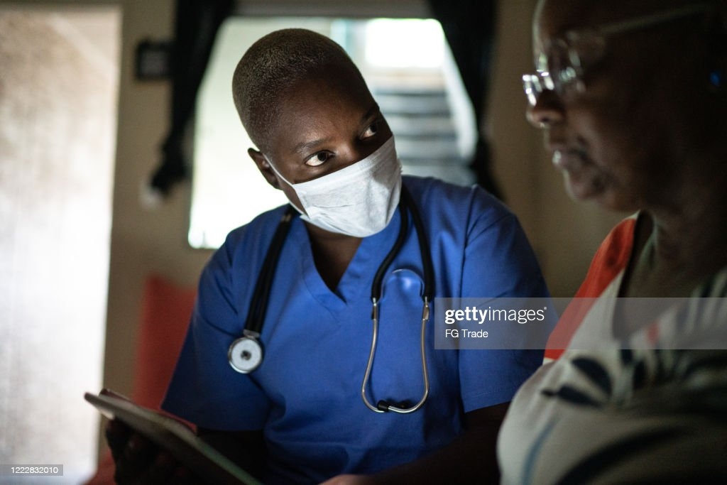 Health visitor and a senior woman during home visit - using digital tablet : Stock Photo