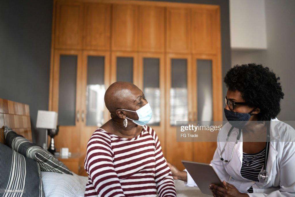 Visitante de saúde e idosa durante visita a asilo : Foto de stock