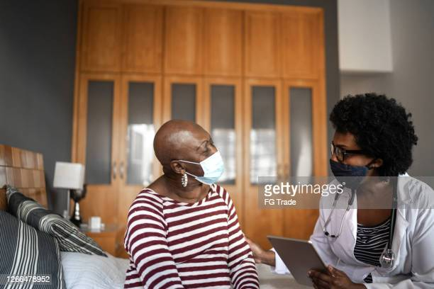 health visitor and a senior woman during nursing home visit - visit stock pictures, royalty-free photos & images
