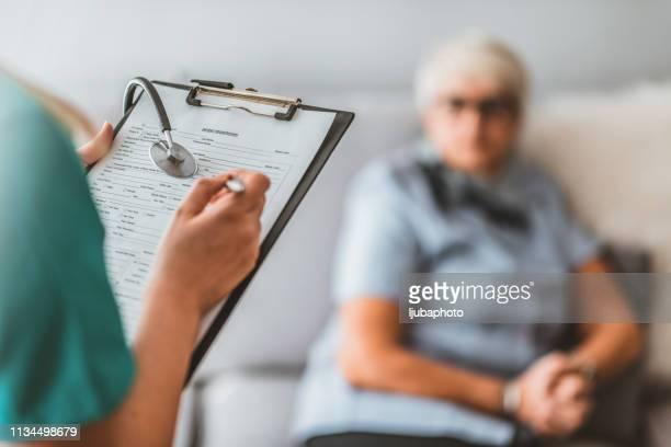 health visitor and senior man during home visit. - examining stock pictures, royalty-free photos & images