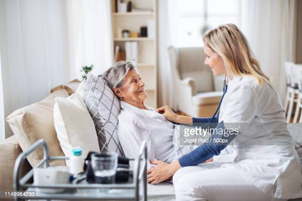 a health visitor examining a sick senior woman lying in bed at home with stethoscope - flat chested woman stock photos and pictures