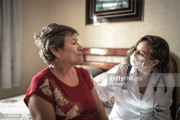 health visitor talking to a senior woman during home visit - south america stock pictures, royalty-free photos & images