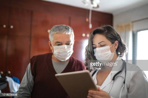 health visitor using digital tablet and talking to a senior man during home visit - protective face mask stock pictures, royalty-free photos & images