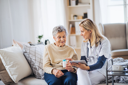 A health visitor with tablet explaining a senior woman how to take pills. 1125363243
