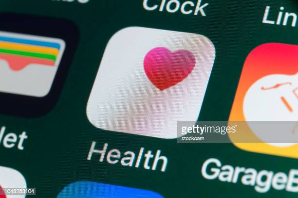 health, wallet, garageband and other apps on iphone screen - mobile app stock pictures, royalty-free photos & images