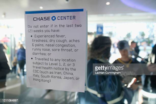 A health warning sign is posted at the entrance to Chase Center before the game between the Golden State Warriors and the Philadelphia 76ers at Chase...