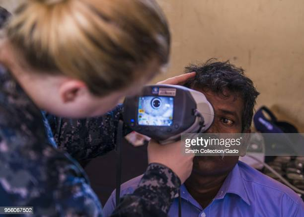 Health worker Abigail Lancely checking the eyes of a native Sri Lankan May 3 2018 Image courtesy Petty Officer 3rd Class Christopher Veloicaza /...