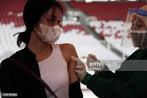 Health worker administer a dose of Cinovac vaccine to a young woman in a mass vaccination in Gelora Bung Karno Stadium, Jakarta, Indonesia on July 3,...