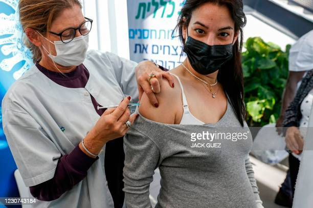 Health worker administers a dose of the Pfizer-BioNtech COVID-19 coronavirus vaccine to a pregnant woman at Clalit Health Services, in Israel's...