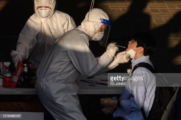 TOPSHOT A health worker administers a swab at a temporary COVID19 novel coronavirus testing centre in Bucheon south of Seoul on May 27 2020 South...