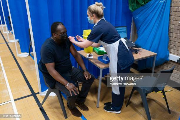 Health worker administers the AstraZeneca Covid-19 vaccine to a man at a mass vaccination centre at Holm View Leisure Centre on March 2, 2021 in...