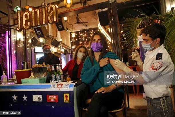 Health worker administers the COVID-19 vaccine to an Israeli at a bar in the coastal city of Tel Aviv on February 18, 2021.