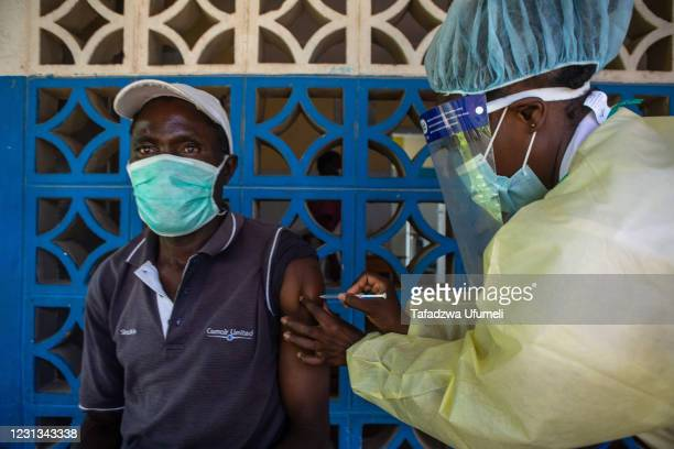 Health worker administers the Sinopharm vaccine to a nurse at Chirau Village Clinic in Zvimba Rural District on February 23, 2021 near Chinhoyi,...
