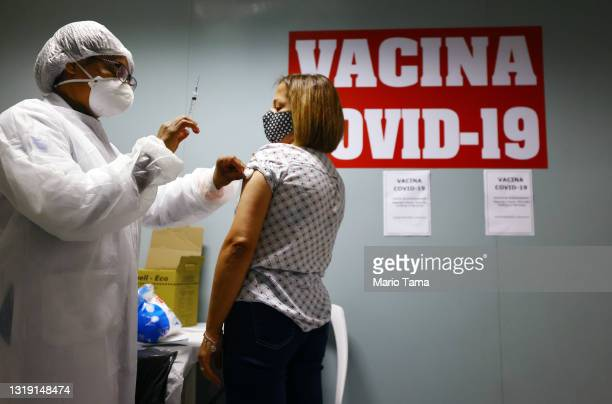 Health worker applies a swab after administering a dose of the COVID-19 vaccine to a person at a vaccination post inside the Republica subway station...