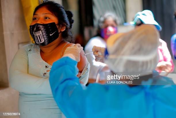 Health worker applies a vaccine against diphtheria to a woman in Lima, on October 28 after a case was detected at a popular district. - Peru has...