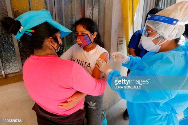 Health worker applies a vaccine against diphtheria to a youngster in Lima, on October 28 after a case was detected at a popular district. - Peru has...
