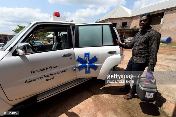 A health worker arrives with a cooler containing blood samples for testing at the Institute of Lassa Fever Research and Control in Irrua Specialist...