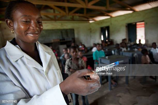 Health worker Blessing holds up an aids speed test strip a strip which shows a negative result no aids Volunteer Blessing and Doofan process the 120...