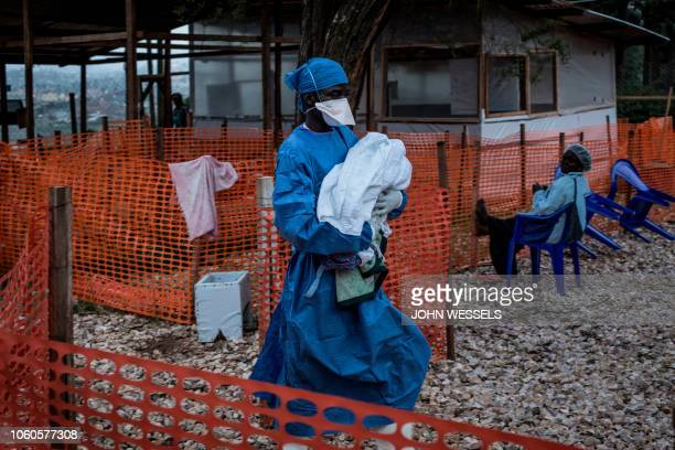 TOPSHOT A health worker carries a fourdayold baby suspected of having Ebola into a MSF supported Ebola Treatment Centre on November 4 2018 in Butembo...