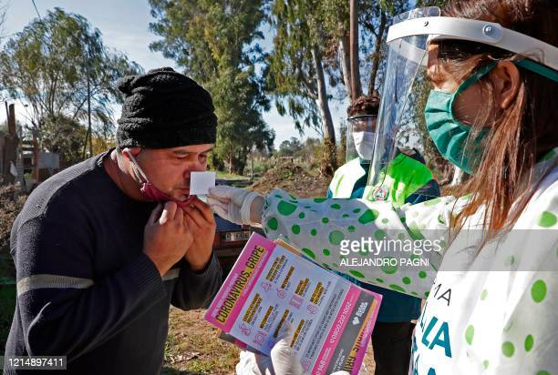 Health worker carries out an olfactory test -to monitor smell loss- to a resident in Altos de San Lorenzo neighborhood, near the city of La Plata, 65...