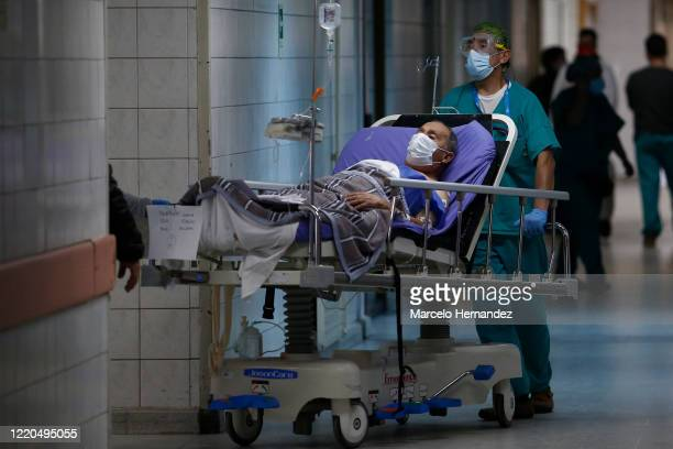 Health worker carry a COVID-19 patient during the coronavirus pandemic at San Jose Hospital on June 16, 2020 in Santiago, Chile. On Monday, President...