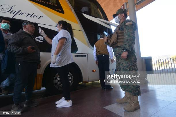 Health worker checks a person's temperature next to a Chilean soldier inside a bus station in Concepcion, Chile, on March 19, 2020. - Chilean...