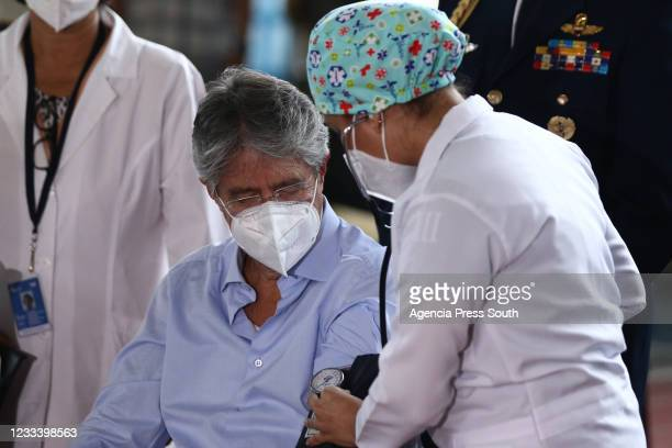 Health worker checks a President of Ecuador Guillermo Lasso blood pressure before receiving a dose of the Pfizer BioNTech vaccine as part of the...