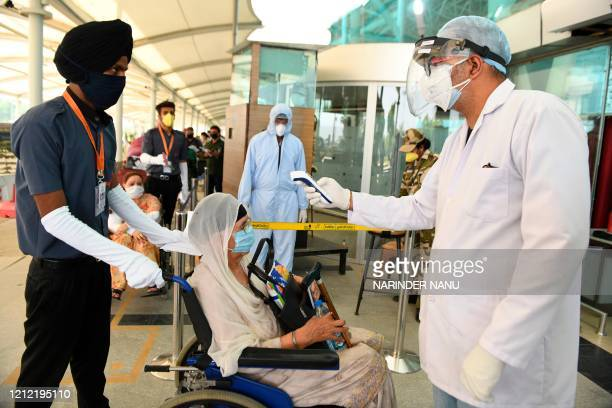Health worker checks the body temperature of a British national queueing before checking-in for a special flight to London after the government eased...