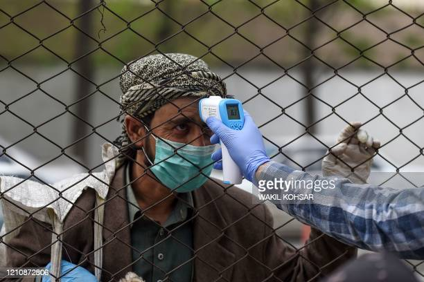A health worker checks the body temperature of a devotee as a preventive measure against the COVID19 coronavirus before the Friday prayers on the...