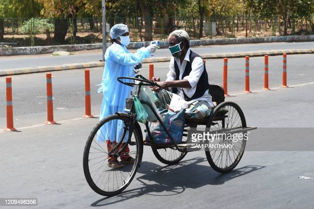 Health worker checks the body temperature of a man with mobility impairment during a government-imposed nationwide lockdown as a preventive measure...